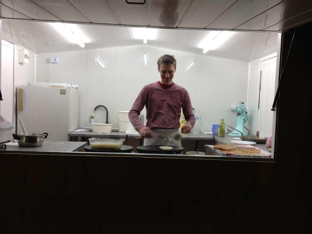Yann dans son châlet à la confection de crêpes Bretonnes dans son chalet ambulant
